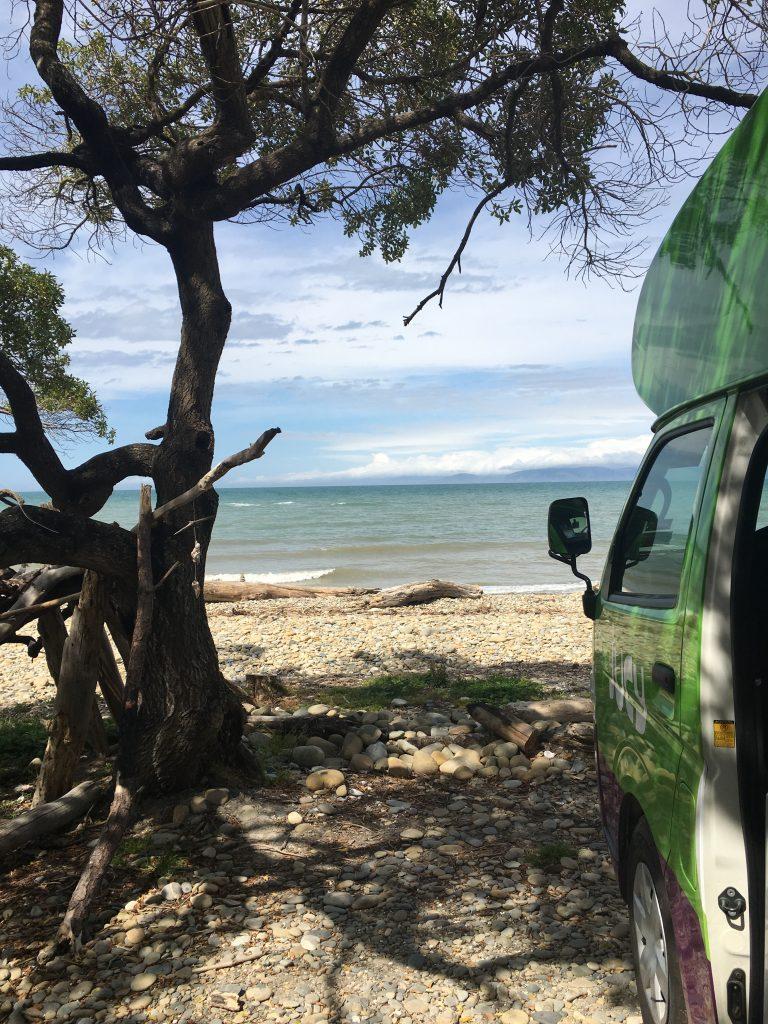 Ein Campervan steht direkt am Meer in Neuseeland.