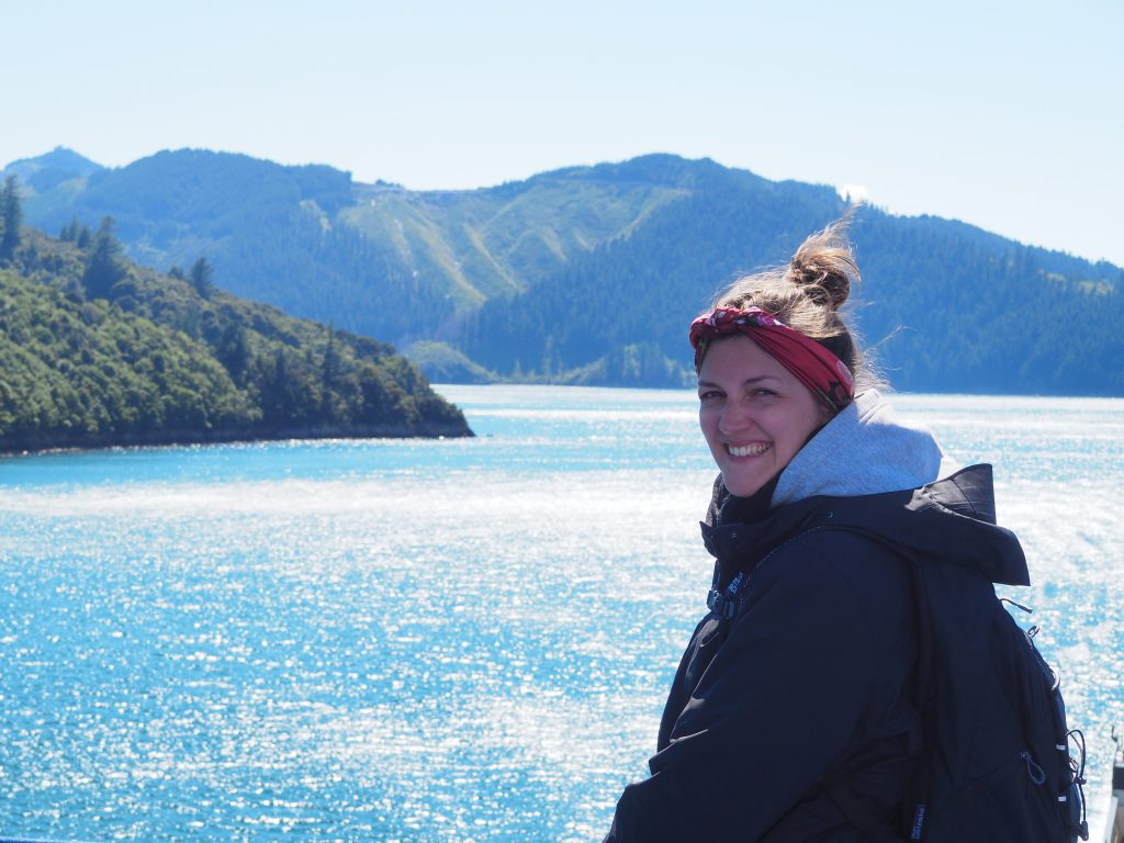 Anna auf der Fähre von Wellington nach Picton. Es sind Berge im Hintergrund zu sehen.