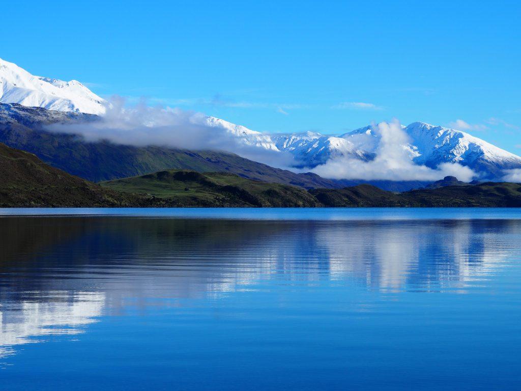 Die schneebedeckten Berge spiegeln sich im See.