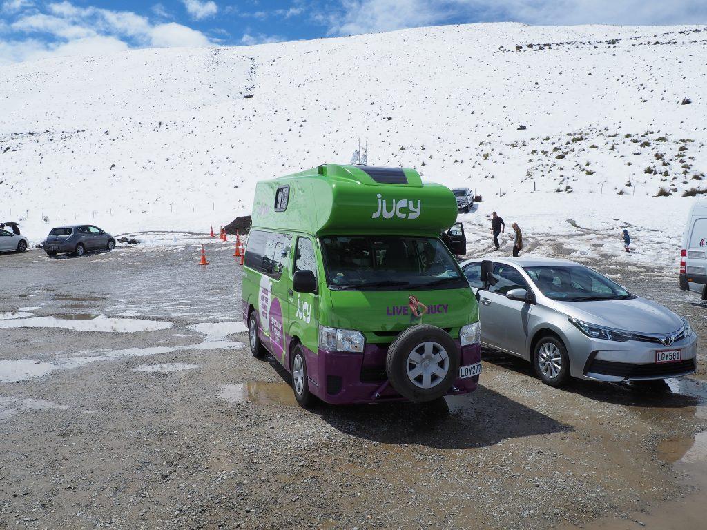 Campervan steht mitten im Schnee.