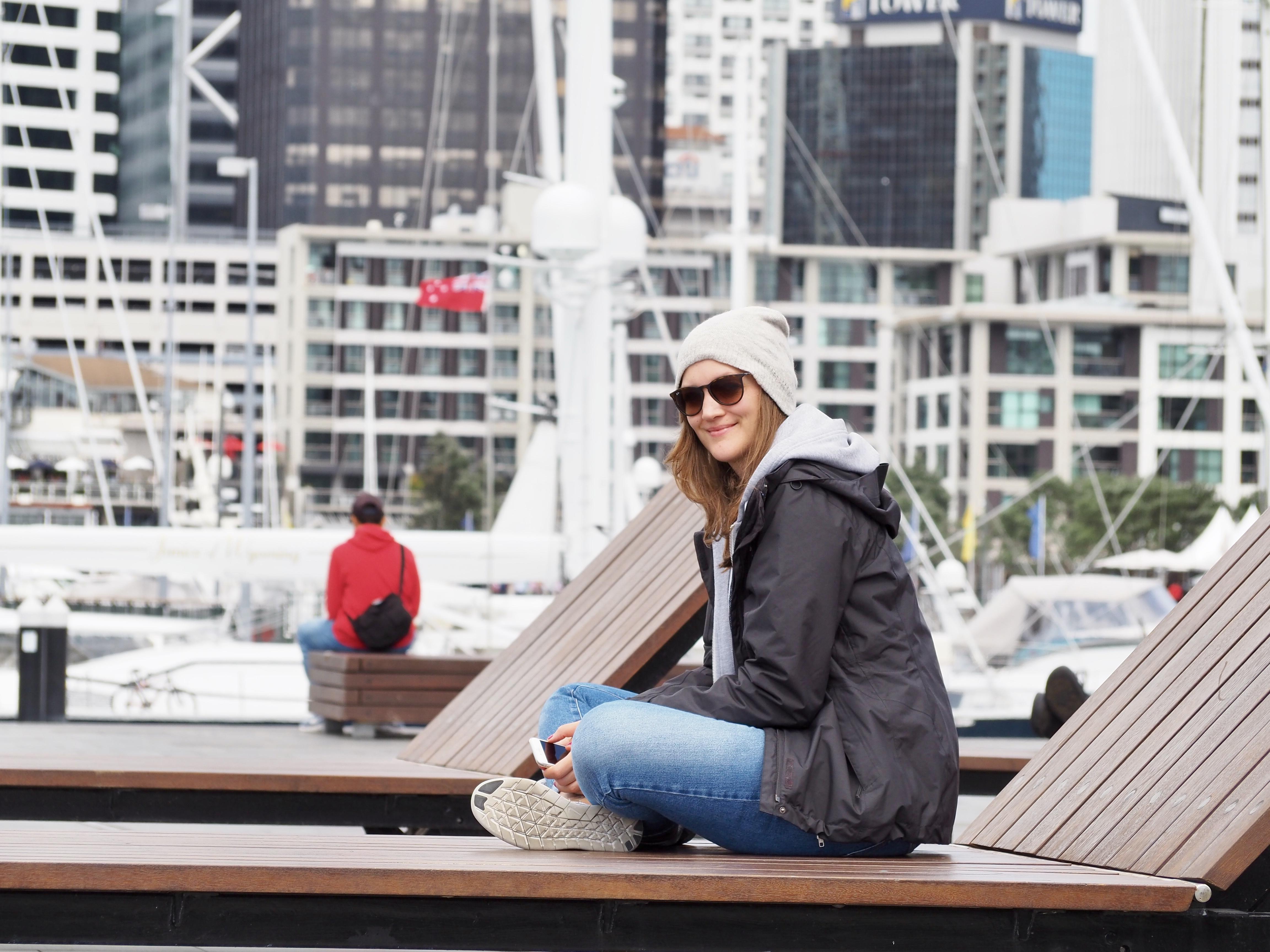 Anna sitzt vor der Skyline am Hafen von Auckland