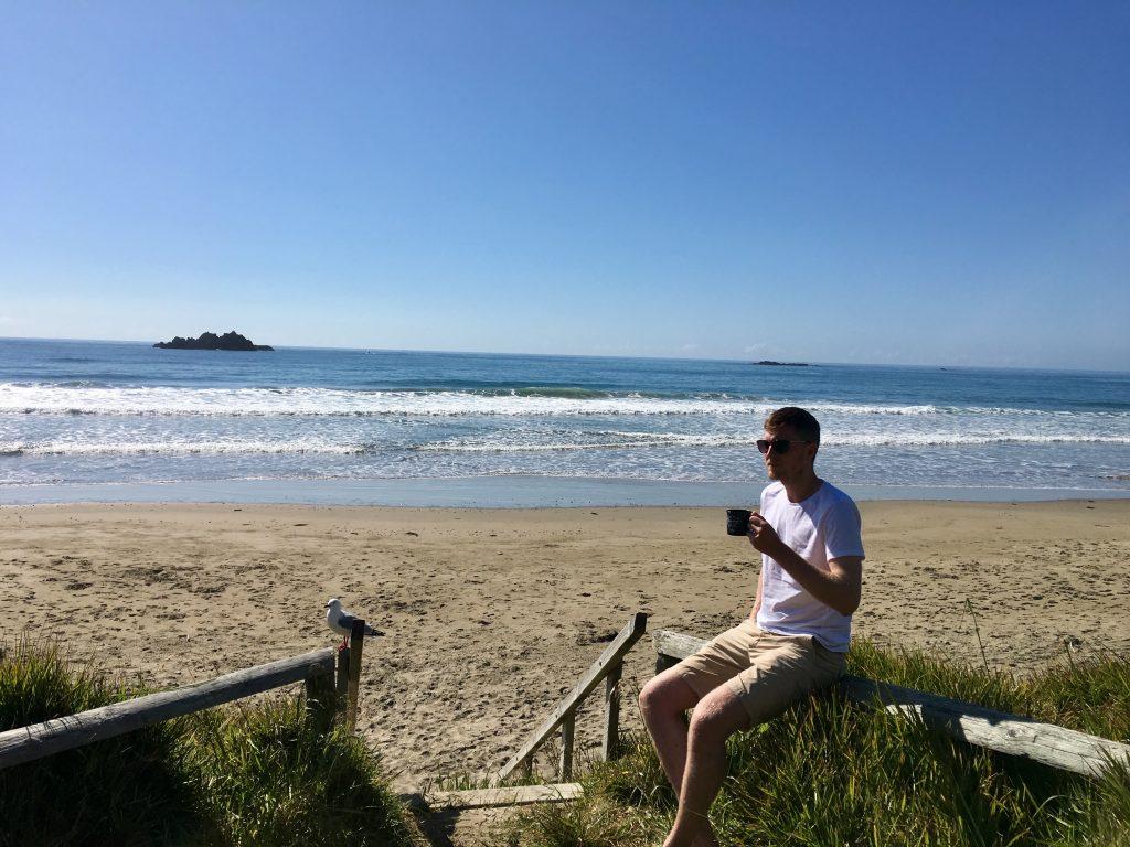 Phillip lehnt mit einem Becher in der Hand an einen Balken am Strand.
