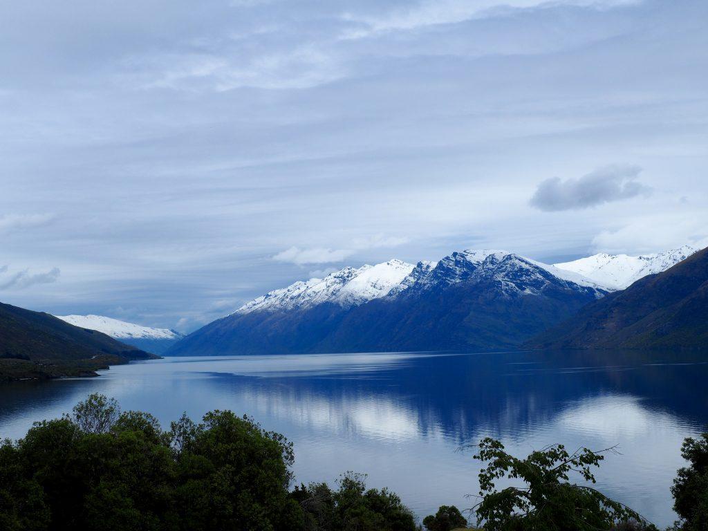 Schneebedeckte Berge spiegeln sich auf einem See.