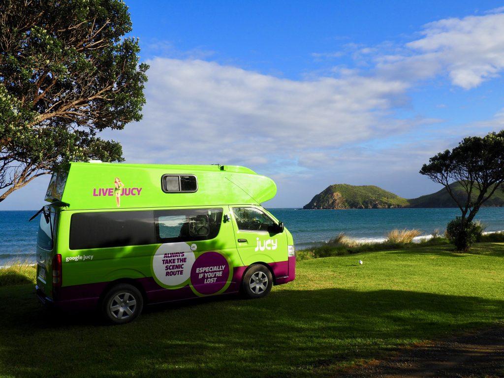 Ein Campervan steht vor dem Meer am Strand von Port Jackson.
