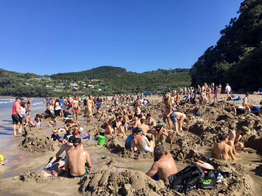 Touristen graben Löcher am Hot Water Beach.