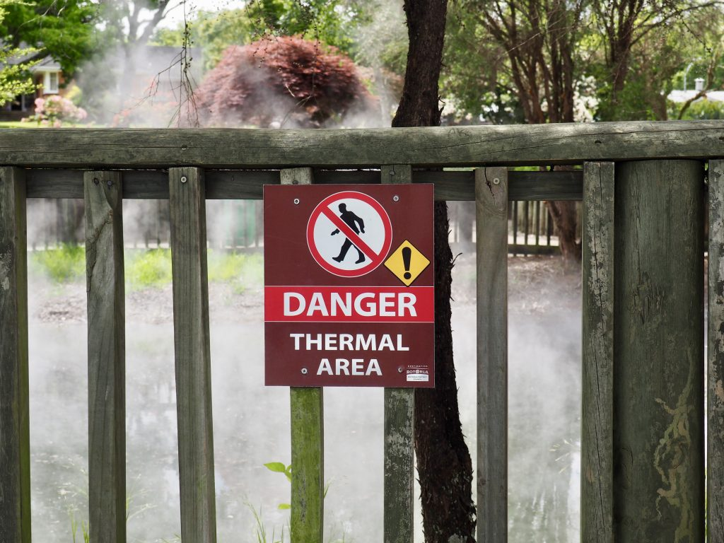 Ein Schild warnt in Rotorua vor geothermischen Aktivitäten.