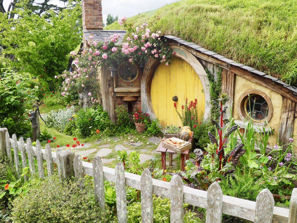 Eine Hobbit-Höhle mit einer gelben Tür und Dekoration.