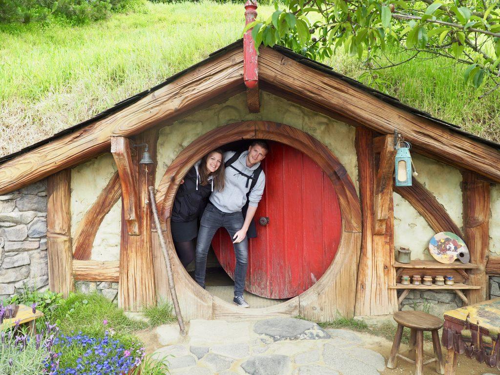 Anna und Phillip schauen hinter der Tür einer Hobbit-Höhle hervor.