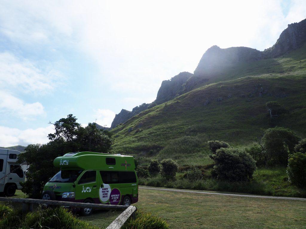 Ein Campervan steht vor einem mit Gras bewachsenen Hang in Kairakau.