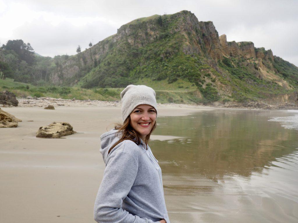Anna lacht am Strand von Kairakau in die Kamera.