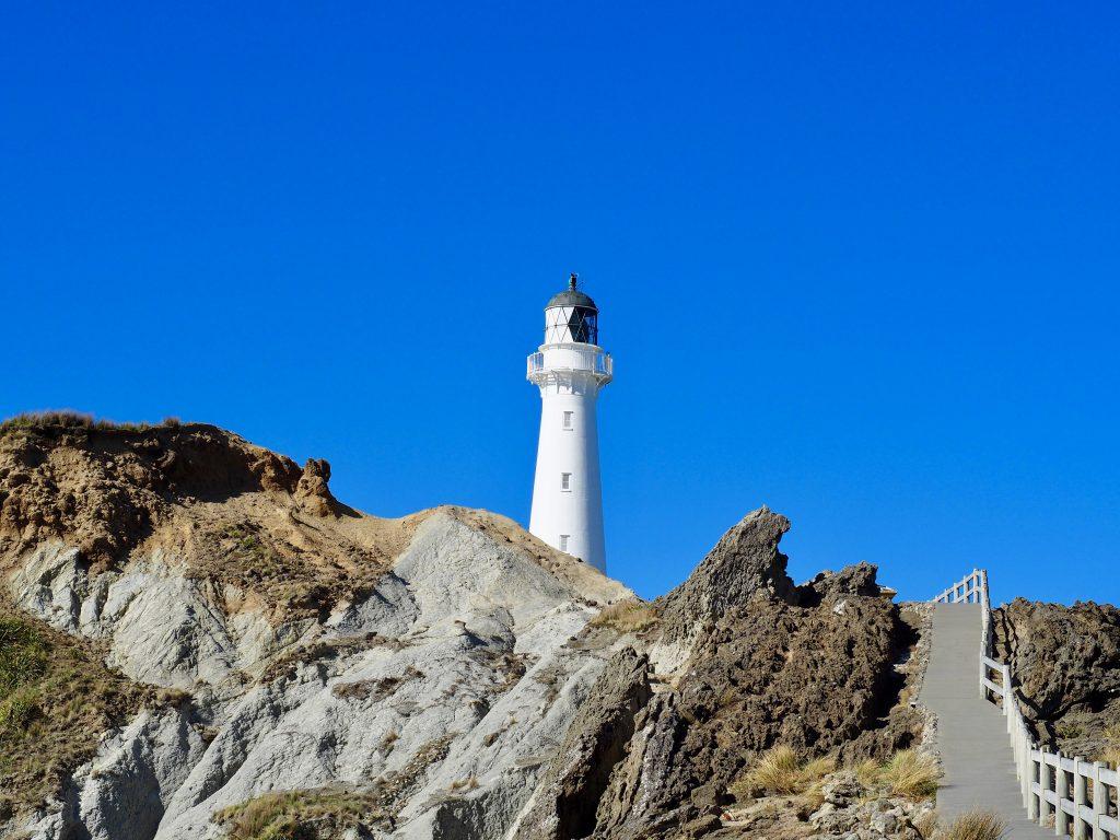 Ein weißer Leuchtturm steht auf Felsen.