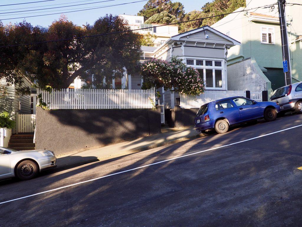 Eine steile Straße mit Häusern und geparkten Autos in Mount Victoria in Wellington.