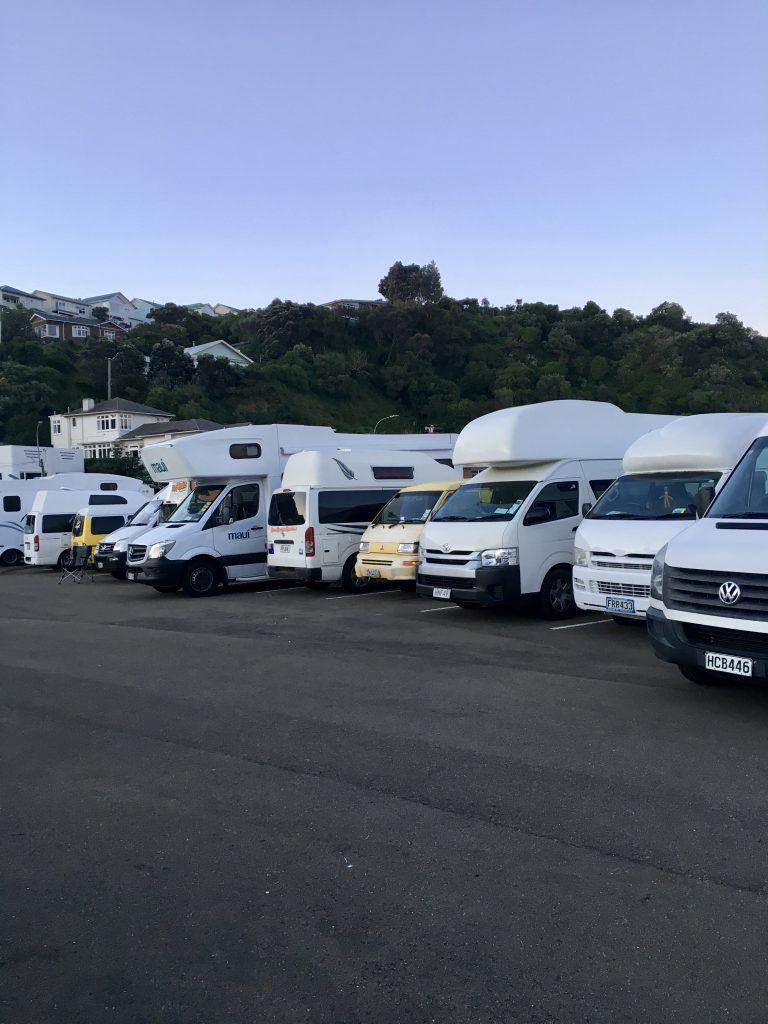 Ein gelber Van mit aktiver Alarmanlage steht in einer Reihe von Wohnmobilen.