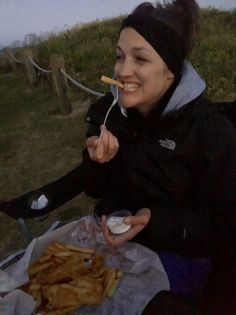 Anna isst Fish and Chips zum Abendessen hinter dem Deich am Waihi Beach.