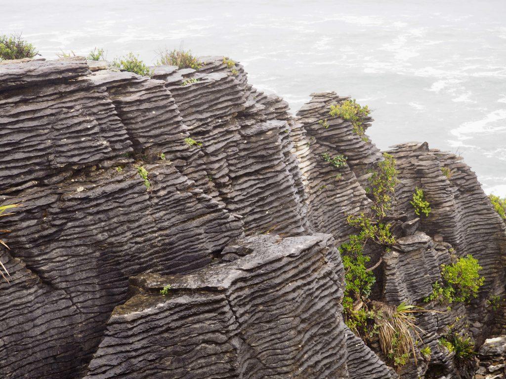 Pancake Rocks bei Regenwetter vor dem unruhigen Meer.