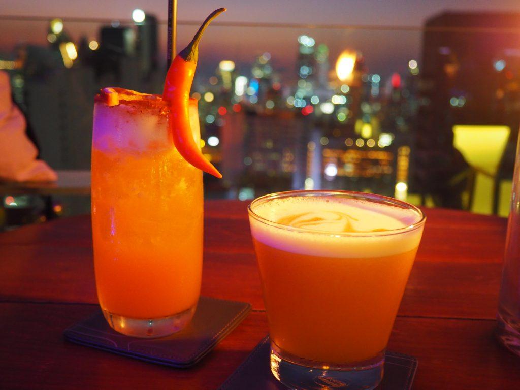 Zwei Cocktails vor den Lichtern Bangkoks im Hintergrund