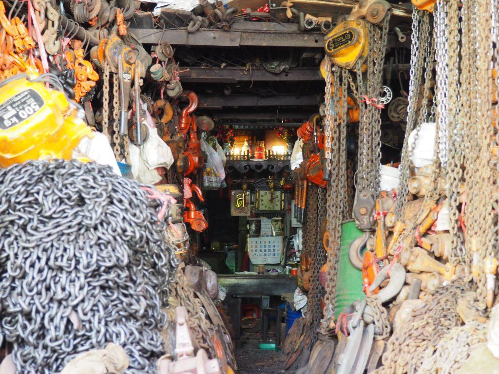 Schwere Metallketten hängen in einem Laden von der Decke. Im Hintergrund ist ein Schrein zu sehen.