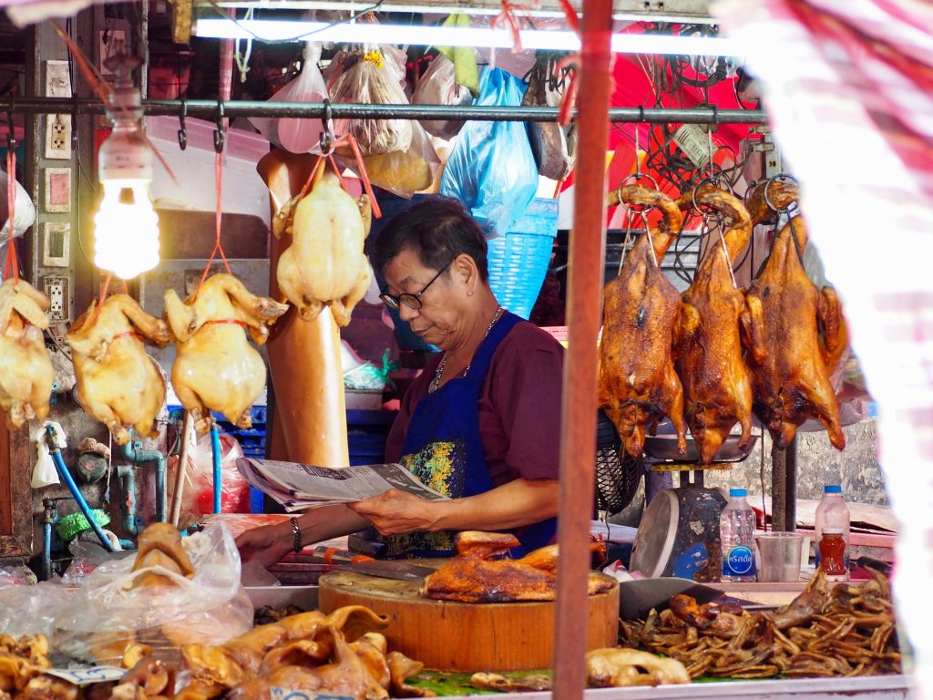 Ein Mann liest an einem Marktstand zwischen gebratenen Enten eine Zeitung.