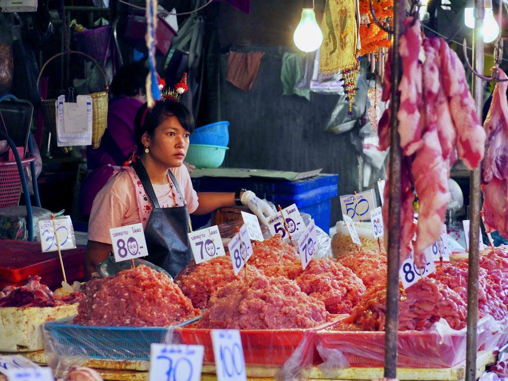 Eine Frau steht hinter Hackfleischhaufen an einem Marktstand.