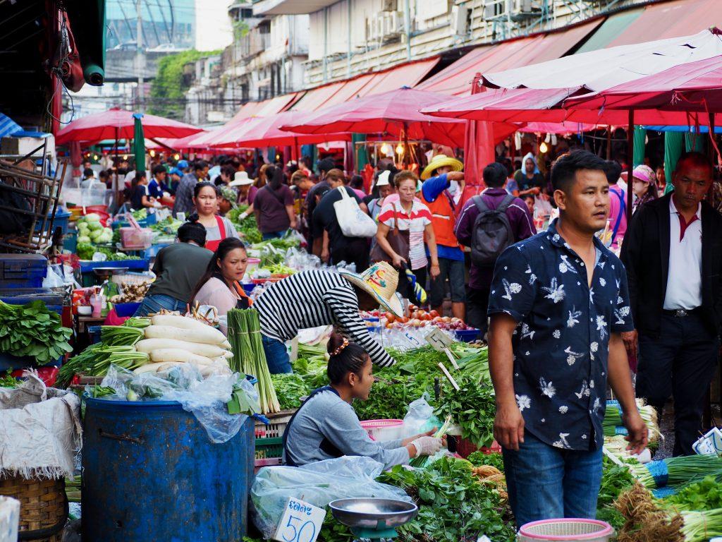 Menschen gehen zwischen Marktständen mit Gemüse umher.
