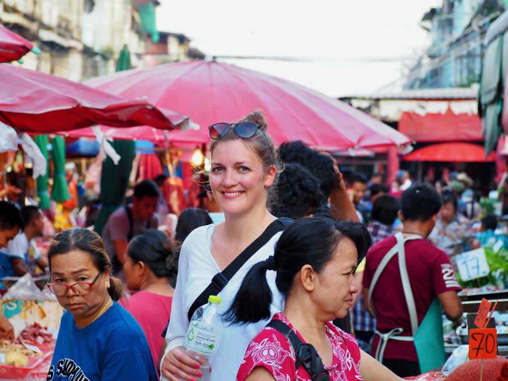 Anna steht zwischen Menschen und Marktständen.