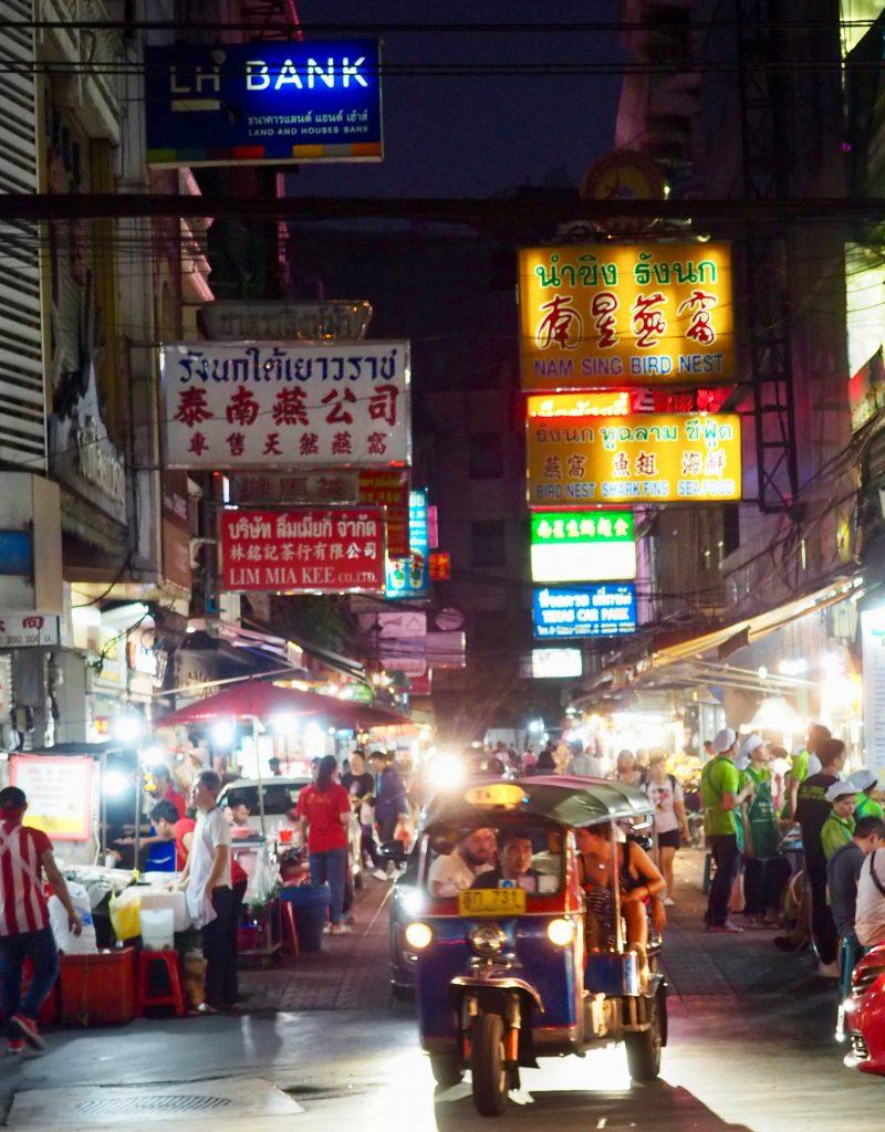 Ein Tuk Tuk fährt aus einer Gasse im abendlichen Chinatown.