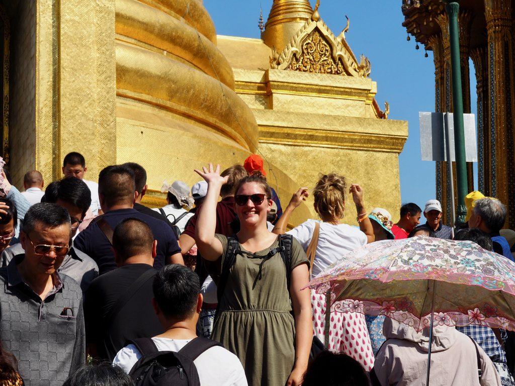 Anna steht in einer Menschenmenge vor Tempeln und winkt.