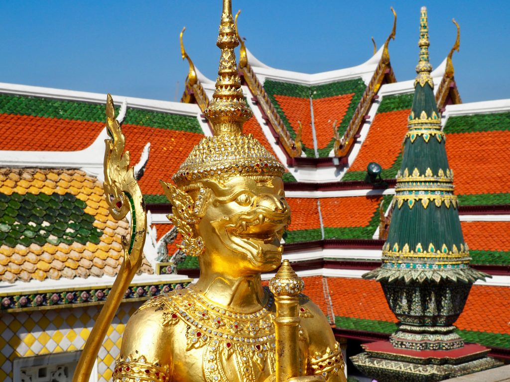 Eine goldene Figur vor Tempeldächern.
