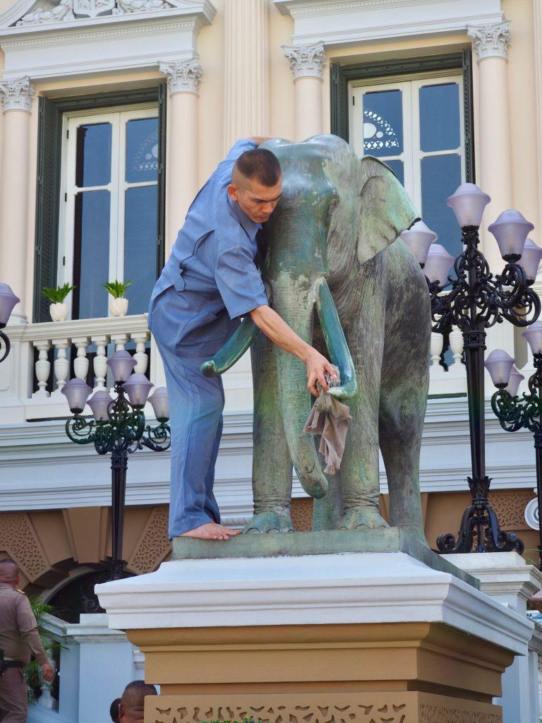 Ein Mann putzt Elefantenstatuen am Königspalast.